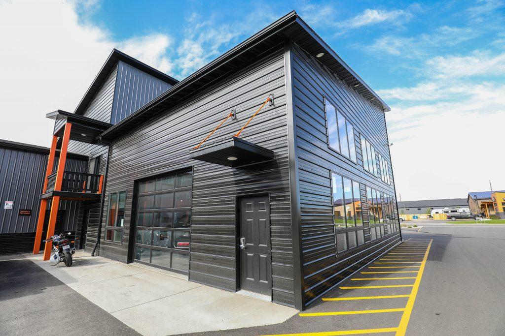 Exterior look of black metal building with glass garage door