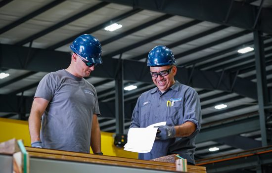 Two ETAS male employees, wearing blue hardhats and safety goggles looking at paper work